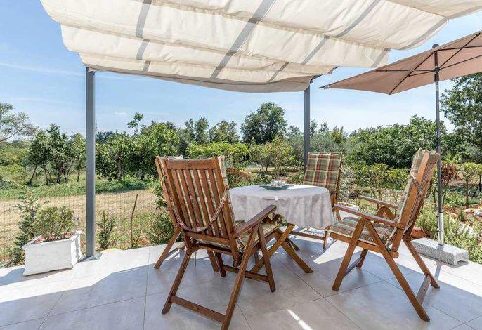 Terrasse mit Sitzgruppe und Sonnenschutz