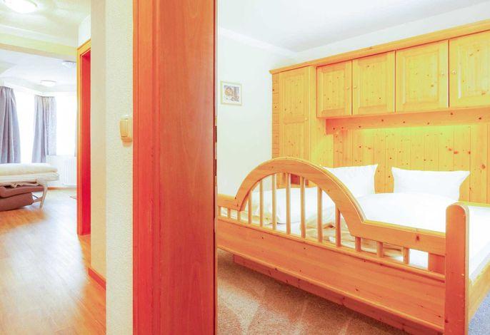 Doppelzimmer mit großem Doppelbett und Wohnschlafbereich