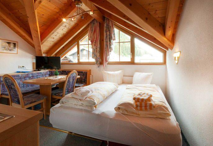 Wohnschlafbereich mit gemütlicher Sitzecke und TV