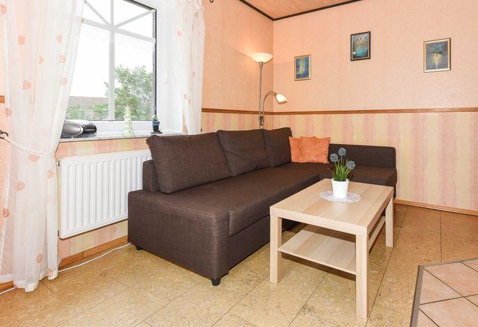 Wohnzimmer mit integrierter Küche und räumlich abgeteiltem Esszimmer-Abteil