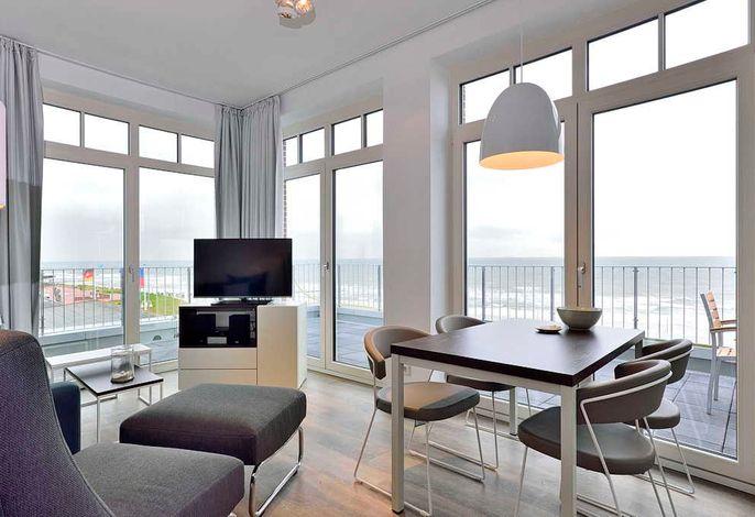 Wohnessbereich mit Esstisch, Sessel und Fernseher