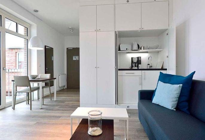 Wohnessbereich mit Couch, Tisch und Küchenzeile