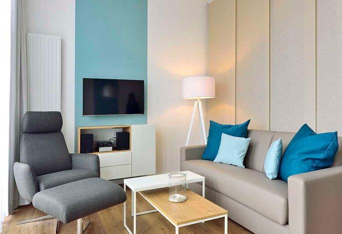 Wohnessbereich mit Couch, Sessel und Fernseher