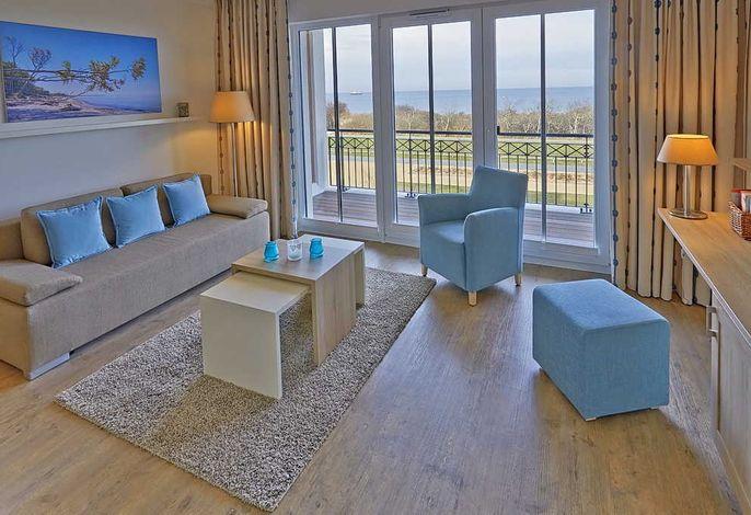 Wohn/Essbereich mit Couch, Couchtisch, Sessel und Zugang zum Balkon