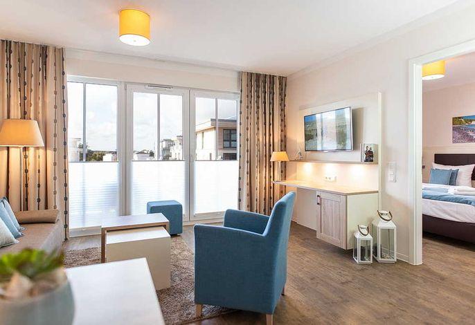 Wohn/Essbereich mit Couch, Couchtisch, Sessel, Tv und Zugang zum Balkon
