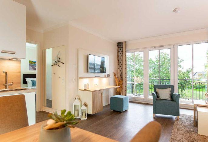Wohn/Essbereich mit Esstisch, Sitzgelegenheiten, Garderobe, TV, und Balkon