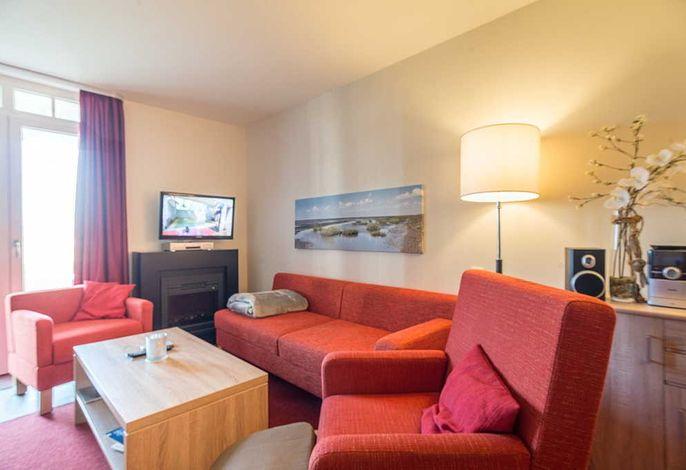 Wohnessbereich mit Couch, Fernseher und Kamin