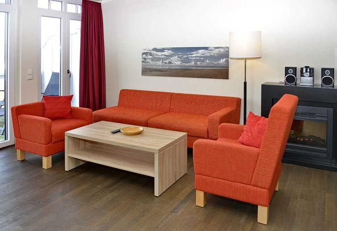 Wohnessbereich mit Couch, zwei Sessel und Kaminofen