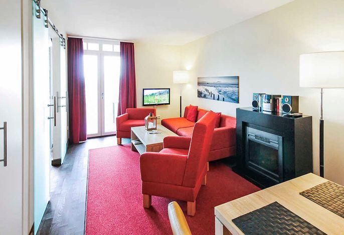 Wohnessbereich mit Couch, Fernseher und Elektro-Kamin