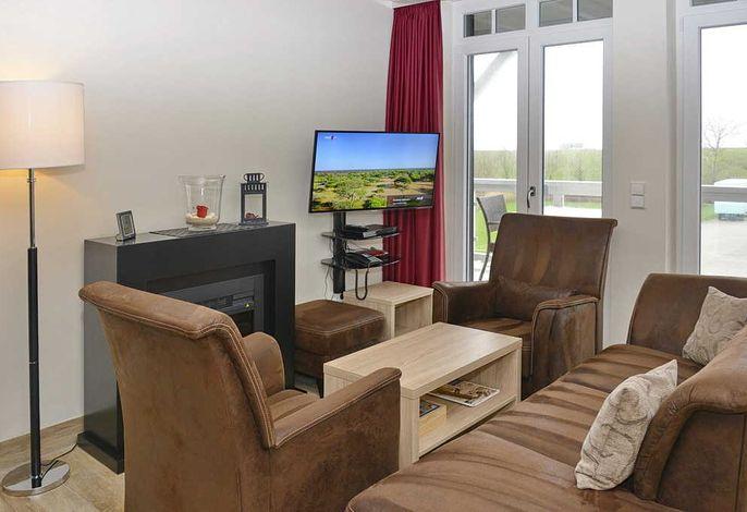 Wohnzimmer mit Couch, zwei Sessel, Kaminofen und Fernseher