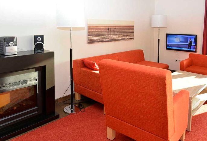 Wohnessbereich mit Couch, Fernseher und Kaminofen
