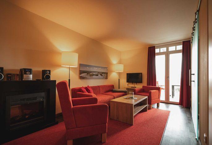 Wohnbereich mit Couch, Sessel und TV