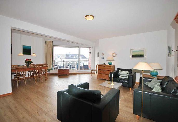 Wohnbereich mit Sesseln, Couch, Esstisch und Zugang zum Balkon