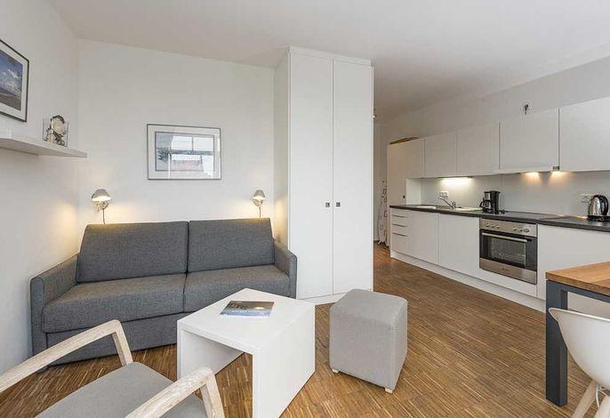 Wohnessbereich mit Couch und Küchenzeile