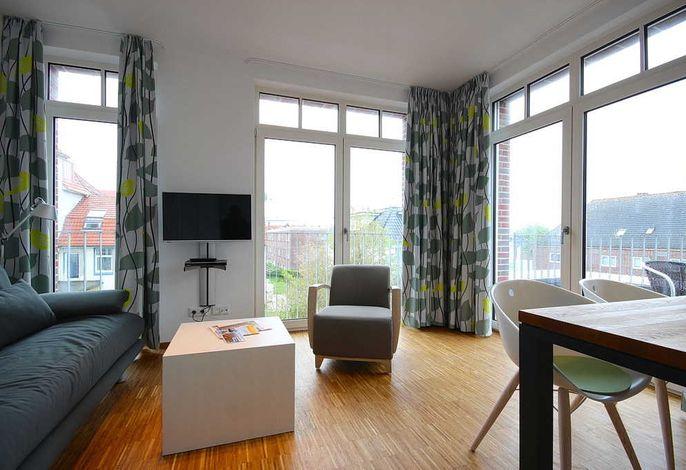 Wohnessbereich mit Couch, Sessel und TV