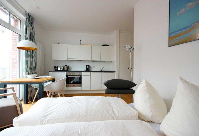 Wohnschlafbereich mit Doppelbett, Esstisch und Küchenzeile