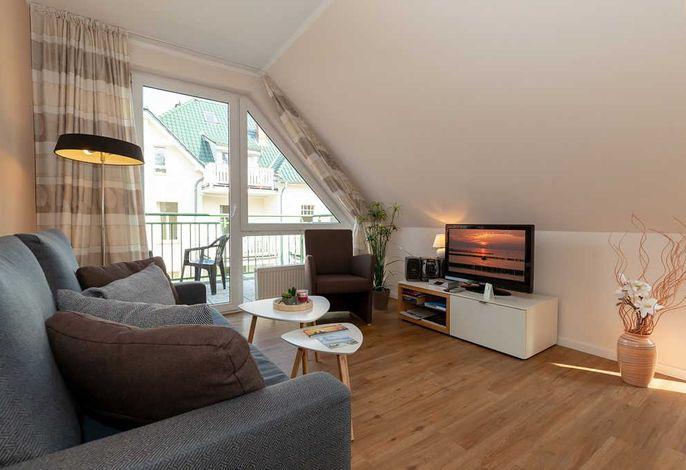 Wohn/Essbereich mit Couch, Sessel, TV und Zugang zum Balkon