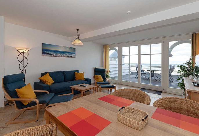 Wohn-/Essbereich mit Sessel, Couch, Esstisch, Sitzgelegenheiten und Zugang zum Balkon