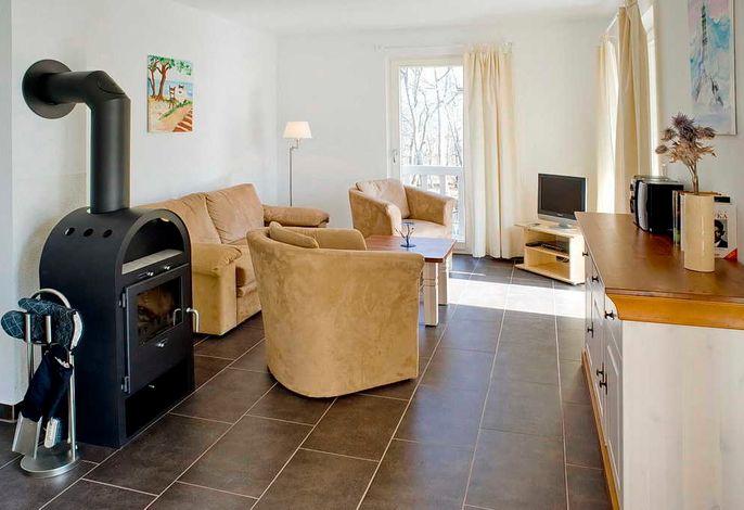 Wohnzimmer mit Couch, Sessel, Kaminofen und TV