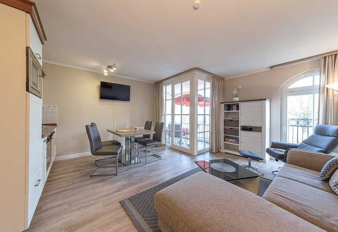 Wohnessbereich mit Couch, Esstisch und Zugang zum Balkon