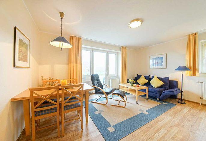 Wohnzimmer mit Esstisch, Couch und Sessel