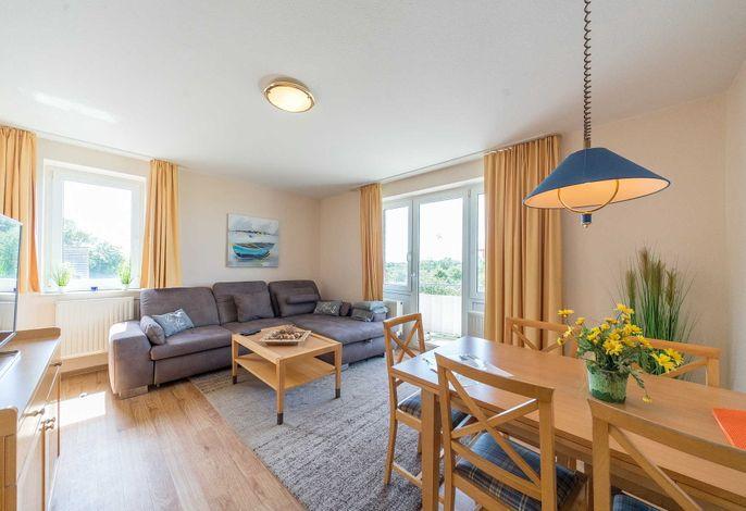 Wohnzimmer mit Couch, Sessel und Esstisch