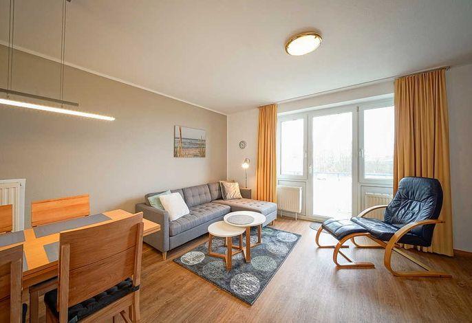 Wohnzimmer mit Couch, Esstisch und Zugang zum Balkon