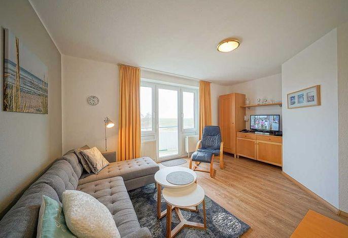 Wohnzimmer mit Couch, Couchtisch, Sessel, TV und Zugang zum Balkon