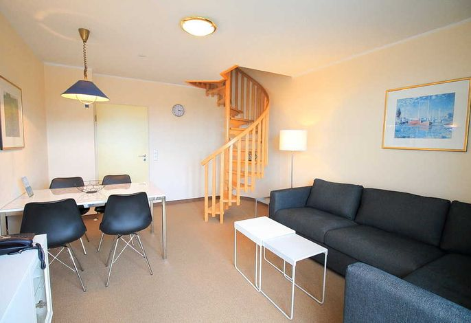 Wohn-/Essbereich mit Couch, Couchtisch und Treppe zur 2. Wohnebene
