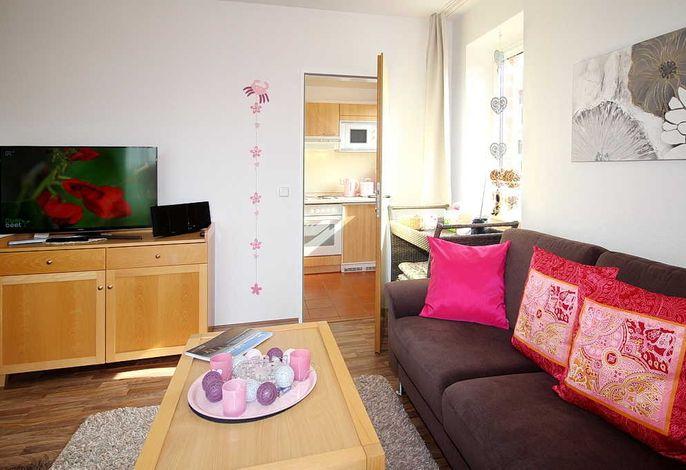 Wohn/Essbereich mit Couch, Schrank und TV