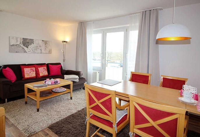 Wohn/Essbereich mit Couch, Tisch, Esstisch und Balkon