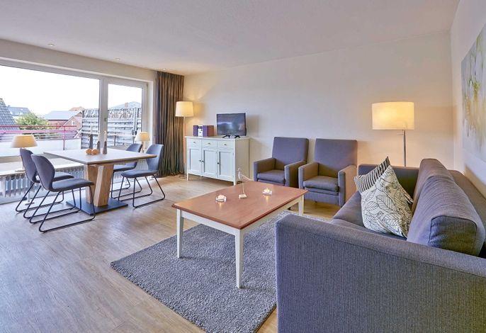 Wohnzimmer mit Couch, zwei Sessel, Esstisch und TV