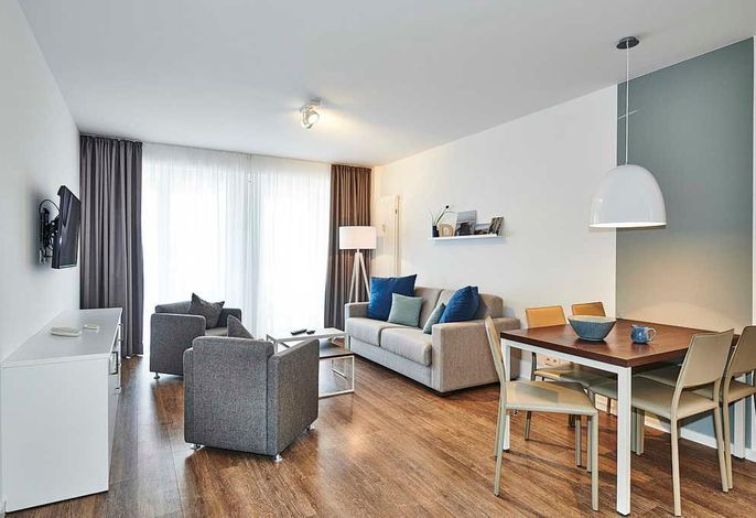 Wohn/Essbereich mit Sesseln, Couch, Esstisch und TV