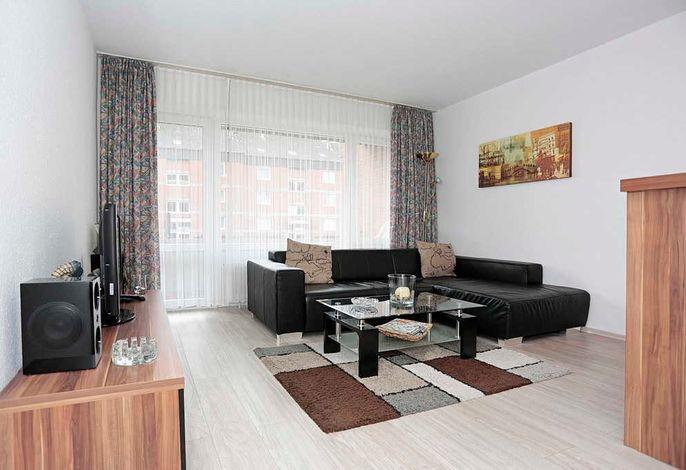 Wohn/Essbereich mit Couch, Tisch und Fernseher