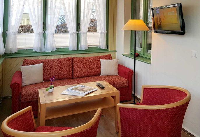 Wohnzimmer mit Couch, Tisch und zwei Sessel