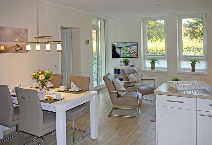 Wohnessbereich mit Esstisch, zwei Sessel und Fernseher