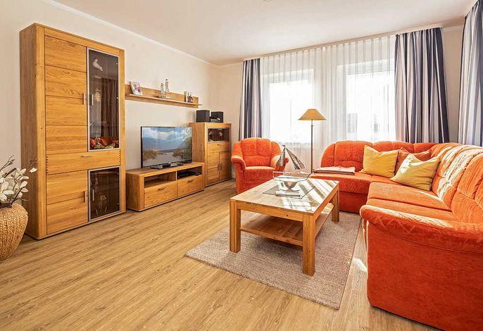 Wohnzimmer mit Couch, Sessel und Fernseher