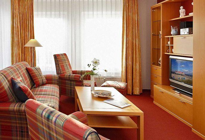 Wohnessbereich mit Couch, zwei Sessel und Fernseher
