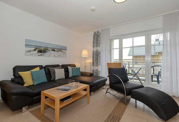 Wohn-/Essbereich mit Sessel, Couch, Couchtisch und Zugang zum Balkon