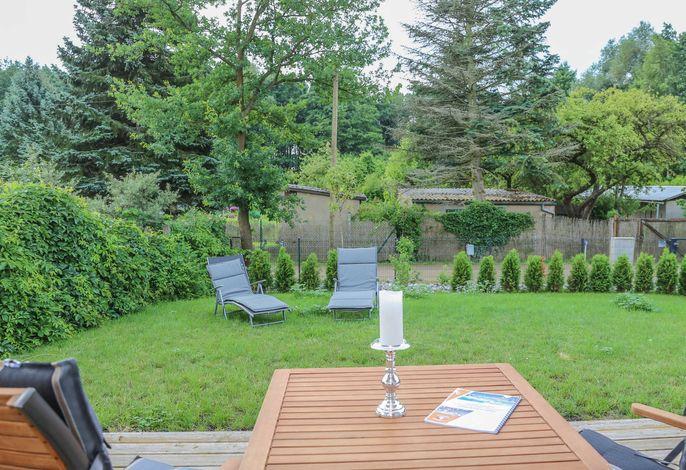 Blick aus dem Ferienhaus auf die Terrasse und den Garten