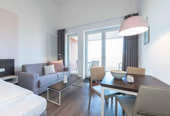 Schlafessbereich mit Doppelbett, Couch und Esstisch