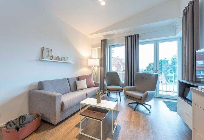 Wohnessbereich mit Couch, Sesseln, TV und Küchenzeile