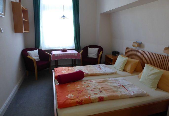 Doppelbett mit bequemen Matratzen,Sitzecke mit Sesseln.