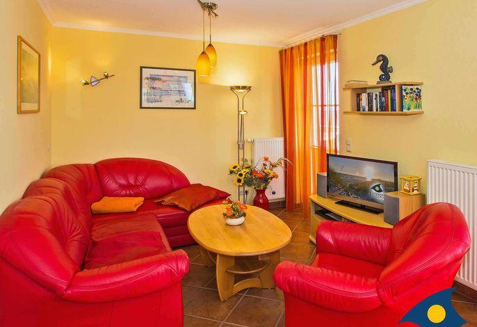 Wohnzimmer mit Zugang zur großen,  teilüberdachten Loggia