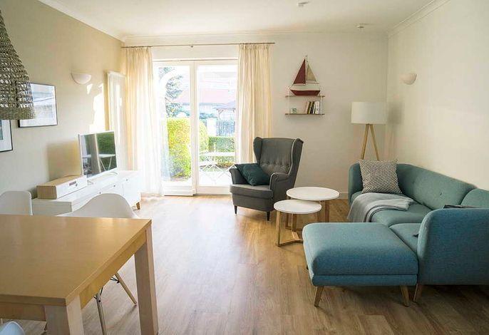 Wohnzimmer mit Couch, Sessel und Zugang zum Balkon