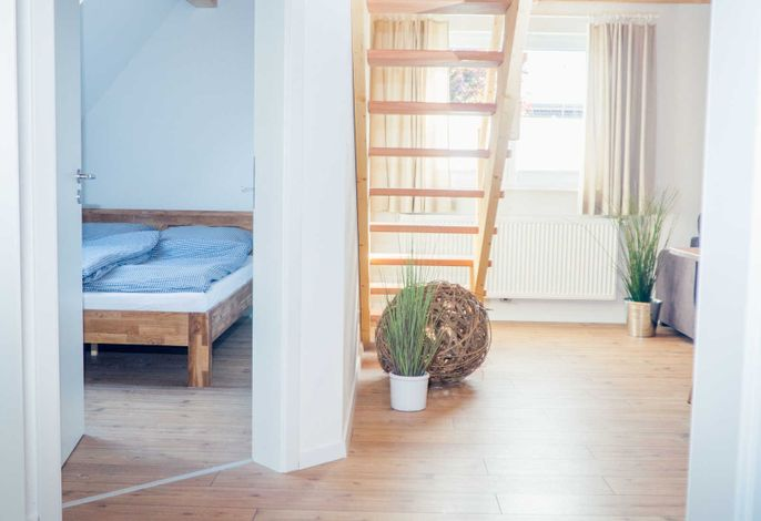 Blick in das separate Schlafzimmer und in den Wohnbereich beim Reinkommen in das Appartement