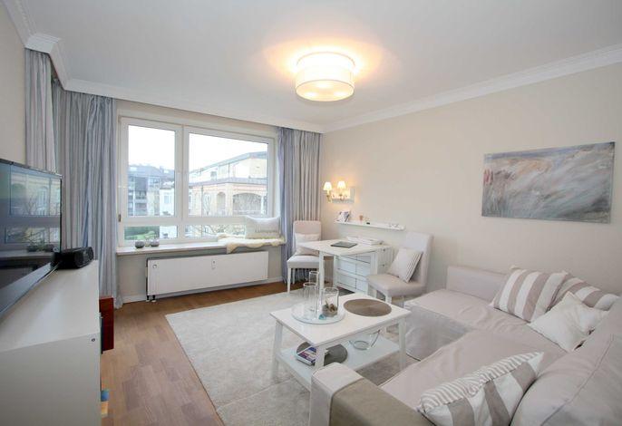 Wohnzimmer mit gemütlicher Couch und Zugang zum Balkon