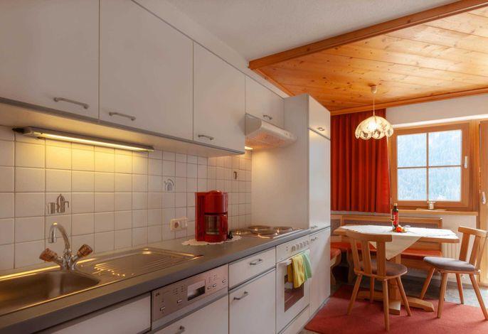 Küche mit Geschirrspüler, Backofen und kleiner gemütlicher Sitzecke