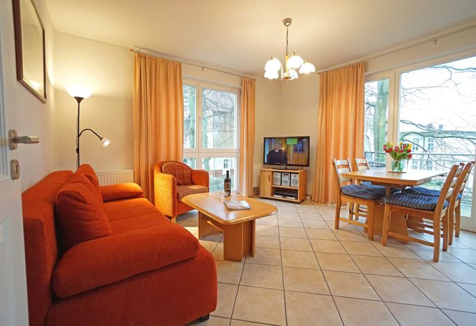 Wohnzimmer mit Schlafcouch, Esstisch und Fernseher