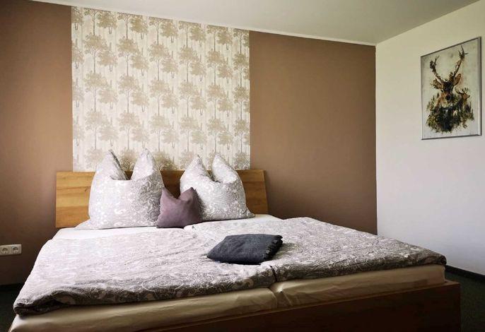 Doppelzimmer mit Doppelbett, Schrank und Esstisch